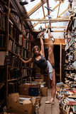 Portrait of ballerina girl in vintage book store wearing casual clothes stock photography