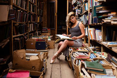 Portrait of ballerina girl in vintage book store wearing casual clothes. And ballet shoes royalty free stock photos