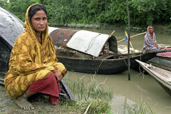 Portrait of Bangladeshi woman in colorful dress. Bangladesh: This young lady is a boat or river nomad. She is squatting on the riverbank. An older woman sit on Stock Photography