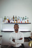 Portrait of bar tender standing with arms crossed at bar counter Royalty Free Stock Photos