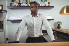 Portrait of bar tender standing at bar counter Royalty Free Stock Images