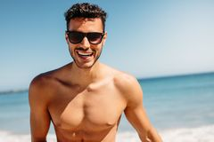 Close up of a shirtless man enjoying at the beach. Portrait of a bare chested tourist having fun at the beach. Shirtless man in sunglasses enjoying near the sea stock photography