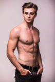 Portrait of bare muscular torso of young man on grey Royalty Free Stock Photos