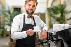 Portrait of barista with coffee cup. Portrait of handsome smiling barista with coffee cup in the cafe Stock Photos