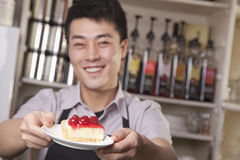 Portrait of barista serving cheesecake Royalty Free Stock Photos