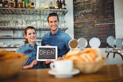 Portrait of baristas holding chalkboard at cafe Royalty Free Stock Photos