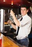 Portrait of barkeeper holding glass at beer dispenser. Portrait of barkeeper holding glass in front of beer dispenser at bar stock images