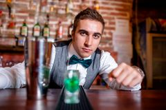 Portrait of barman behind bar with cocktail tools and drinks Stock Photo