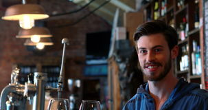Portrait of barman holding two glasses of red wine at bar counter. In pub stock video footage