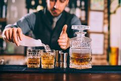 Portrait of barman adding ice to delicious alcoholic whiskey cocktails. Portrait of bartender adding ice to delicious alcoholic whiskey cocktails stock images