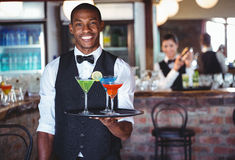 Portrait of bartender holding serving tray with cocktail glasses royalty free stock images