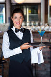 Portrait of bartender holding serving tray with glass of cocktail stock photo