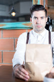 Portrait of bartender looking at camera while holding paper bag Stock Images