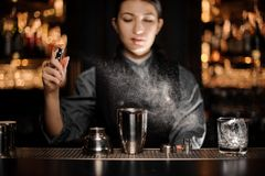 Portrait of bartender pouring cocktail with shaker and sprayer. Portrait of female bartender pouring alcohol cocktail with shaker and sprayer royalty free stock photo