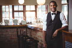 Portrait of bartender standing at bar counter. Portrait of smiling bartender standing at bar counter Royalty Free Stock Image