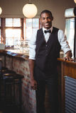 Portrait of bartender standing at bar counter. Portrait of smiling bartender standing at bar counter Royalty Free Stock Photos