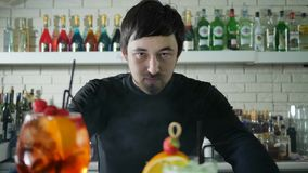 Portrait of bartender beside vivid alcohol beverage with berries on background of bar interior with colored bottles. In white mist stock footage