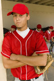 Portrait Of Baseball Player With Teammates In Background. Portrait of a young baseball player with teammates sitting in dugout in background Royalty Free Stock Photo