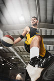 The portrait of a basketball player with ball against gray gym background Stock Image