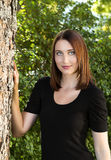 Portrait of a bautiful young woman. Portrait of a pretty young woman leaning against a tree Royalty Free Stock Images