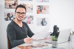 Happy man working with pictures stock photo