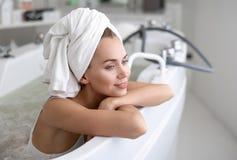 Positive lady leaning on bath stock photo