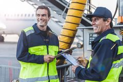Cheerful technical staff having job at airport stock photography