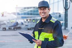 Cheerful worker writing document at airport Stock Photo