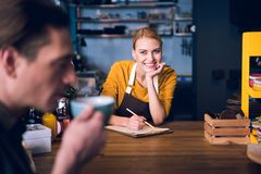 Smiling barista watching at client. Portrait of beaming worker writing on paper in clipboard while looking at visitor. He drinking mug of hot tea in cafe Stock Photo