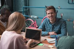 Smiling man situating near colleagues at desk royalty free stock photos