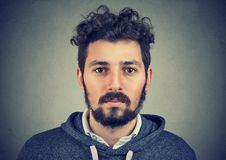 Portrait of a beard man with serious face expression. On gray wall background Stock Photography