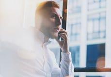Portrait bearded adult businessman working on modern loft office. Man wearing white shirt and using smartphone. Panoramic windows background. Horizontal Stock Photography