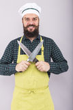 Portrait of a bearded angry man holding two big sharp knives Royalty Free Stock Images