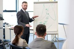Mature Business Coach at Whiteboard. Portrait of bearded business coach standing by whiteboard giving presentation for audience and pointing at statistics graphs Stock Photo
