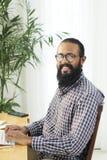 Bearded businessman working on computer stock photos