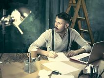 Portrait of a bearded businessman who is working with his notebook at loft studio. Stock Photos