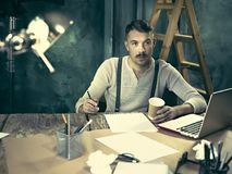Portrait of a bearded businessman who is working with his notebook at loft studio. Royalty Free Stock Photography