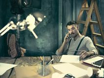 Portrait of a bearded businessman who is working with his notebook at loft studio. Royalty Free Stock Images