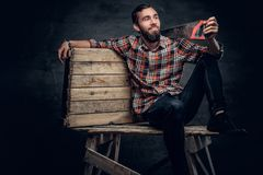 Portrait of bearded carpenter male holds handsaw on a shoulder. Portrait of bearded carpenter male dresses in a plaid shirt and jeans holds handsaw on a Stock Photography