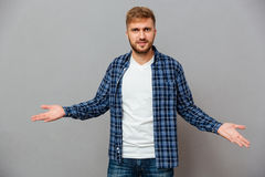 Portrait of a bearded casual man shrugging shoulders Royalty Free Stock Image