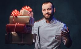 Chef cook holds colorful paper Christmas gifts. Royalty Free Stock Image