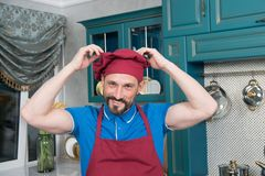 Portrait of man wears cap at kitchen. Guy loves hat and cooking.Bearded chef dressed on the red hat. Royalty Free Stock Photo