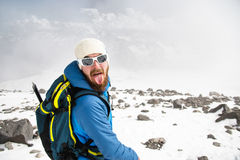 Portrait of a bearded guide wearing a hat and sunglasses shows his tongue stock images