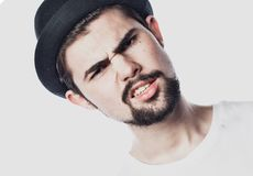 Portrait of bearded guy wearing black hat with unhappy expression on face. Over white background Royalty Free Stock Photo