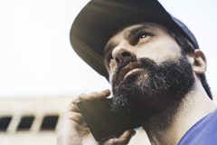 Portrait of bearded handsome man using his smartphone on the street. Blurred background. Horizontal. Portrait of bearded handsome man using his smartphone on Royalty Free Stock Photo