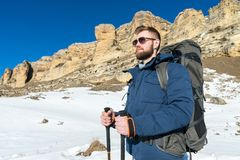 Portrait A bearded hipster with a backpack and in sunglasses with a large backpack on his shoulders stands with sticks. For Nordic walking on the background of Royalty Free Stock Image