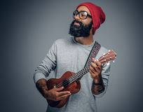Bearded hipster male in red hat playing on ukulele. stock photo