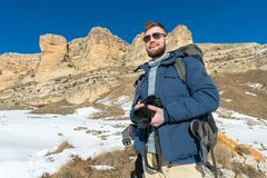 Portrait A bearded hipster photographer with a backpack and wearing sunglasses with a large backpack on his shoulders. Stands with a DSLR camera in his hands Royalty Free Stock Photography