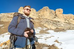 Portrait A bearded hipster photographer with a backpack and wearing sunglasses with a large backpack on his shoulders. Stands with a DSLR camera in his hands Stock Photography