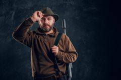 Portrait of a bearded hunter with rifle holding hand on hat and looking at a camera. stock photo